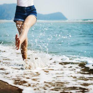 happy woman splashing on beach
