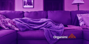 self-care: woman lying on couch with blanket covering her body